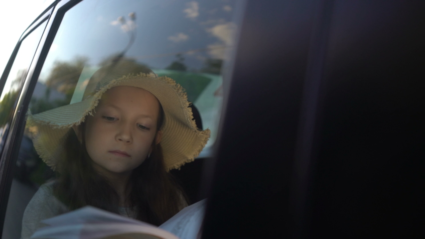 Girl with straw hat Reading Book Inside Car in backseat. road trip concept