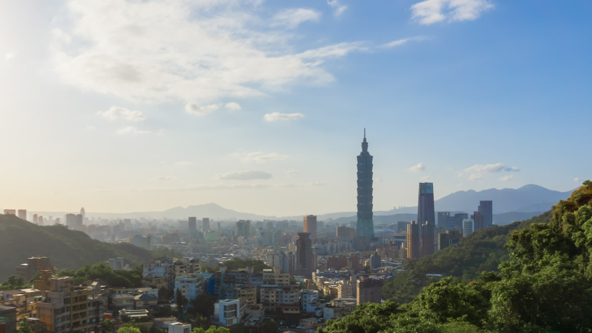 Beautiful aerial time lapse view of Taipei city skyline and skyscrapers during blue sky day from afar with surrounded green mountains. Zoom out motion timelapse.