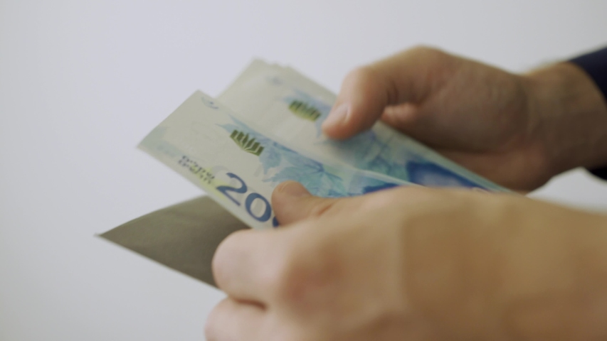 Hands take out Israeli money bills from black envelope and count it | Shutterstock HD Video #1029758090