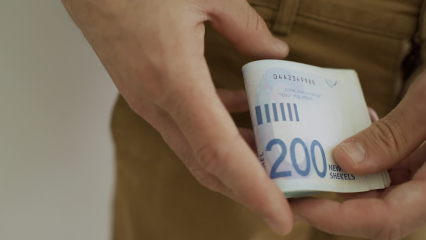 Man counts Israeli bills and puts them inside his pocket #1029758132