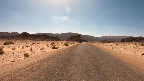Driving footage on an empty old Desert road in wide view and lens flare.