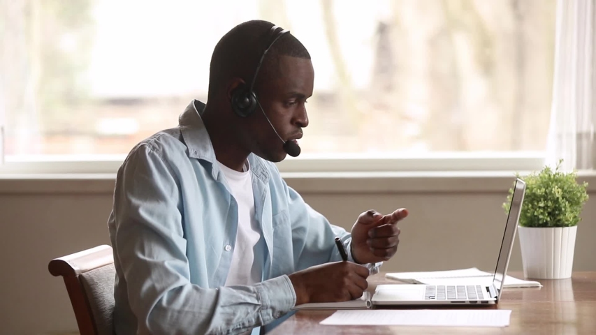 Focused african business man wear headset look at laptop screen make conference video call notes, serious black student learn study with online  teacher on computer, distance education concept