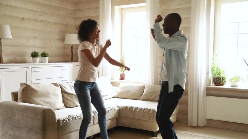 Young romantic black couple dancing in modern living room enjoying funny party at home, happy active african man and woman having fun at party celebrate new house purchase mortgage investment concept