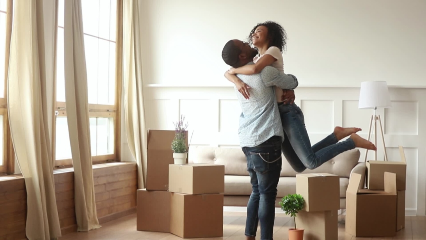 Happy african couple renters owners tenants celebrate moving day in own flat house, excited black man husband holding carrying spinning woman wife having fun among boxes enjoy relocation into new home Royalty-Free Stock Footage #1029780962