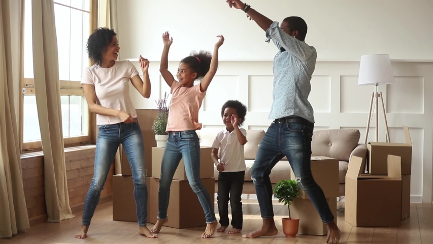 Happy active african american family parents and cute funny kids dancing jumping laughing in modern living room with boxes, black mom dad with little children celebrating moving day in new house Royalty-Free Stock Footage #1029780965