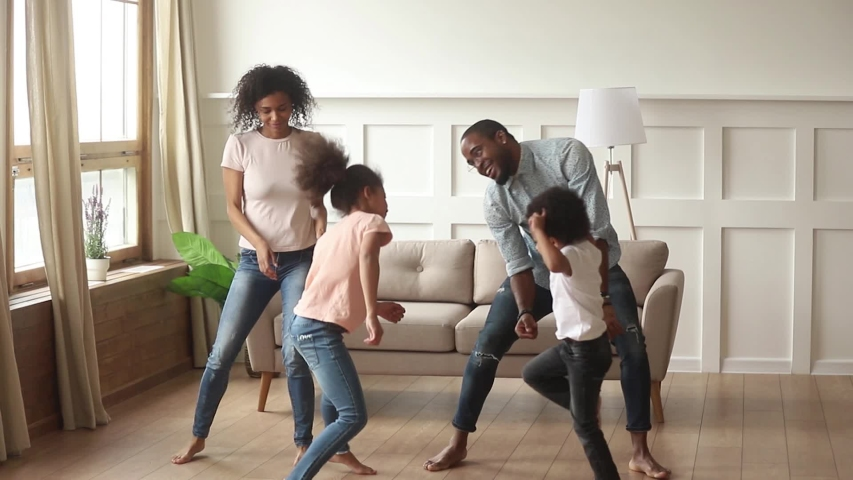 Carefree active black parents and small cute kids dancing together in living room, happy african family mom dad with little funny kids laughing having fun jumping enjoying leisure weekend activity  | Shutterstock HD Video #1029780968