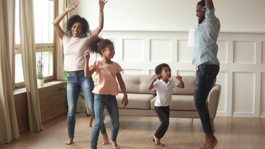 Happy african american parents and cute funny kids dancing laughing in living room, black mom dad with little children enjoying jumping having fun together, family of four funny leisure activity | Shutterstock HD Video #1029780983