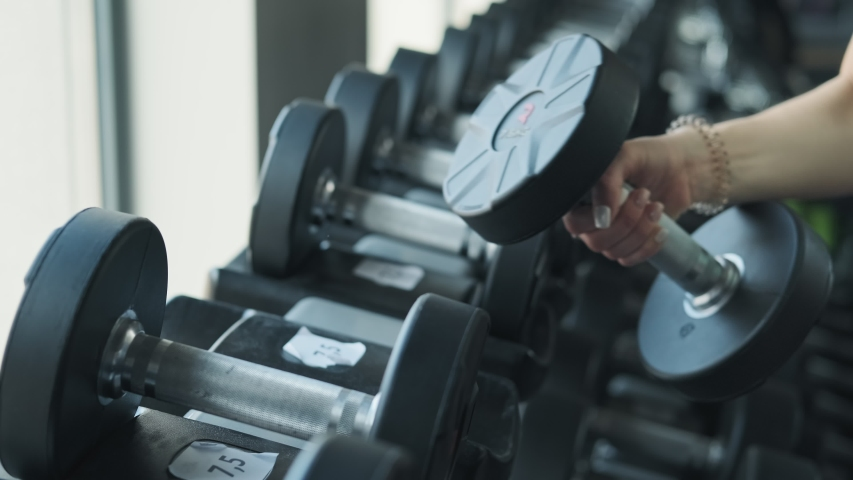 Close up shot of young sportive woman in sportswear taking dumbbell from stand in gym | Shutterstock HD Video #1029787949