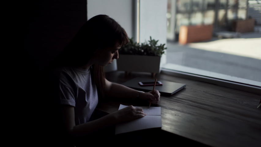Left hand of a young woman draw with a pencil on paper close up. Girl makes sketches in a cafe in front of the window. On the table are her gadgets - phone and laptop. Young female is wearing a watch | Shutterstock HD Video #1029792359
