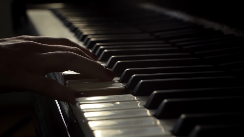 Woman pianist plays gentle classical music on a beautiful grand piano with one hand close-up in slow motion. Piano keys close up in dark colors. Student trains to play the piano