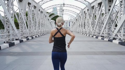 Young asian woman runner running on city bridge road with cityscape on  background. Sport lifestyle.