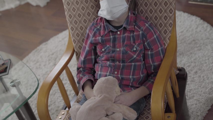 Portrait small ill boy sitting in the armchair with a medical mask on his face holding the toy at home. Different pills lying on the table on the background. Concept of healthcare. | Shutterstock HD Video #1029813005