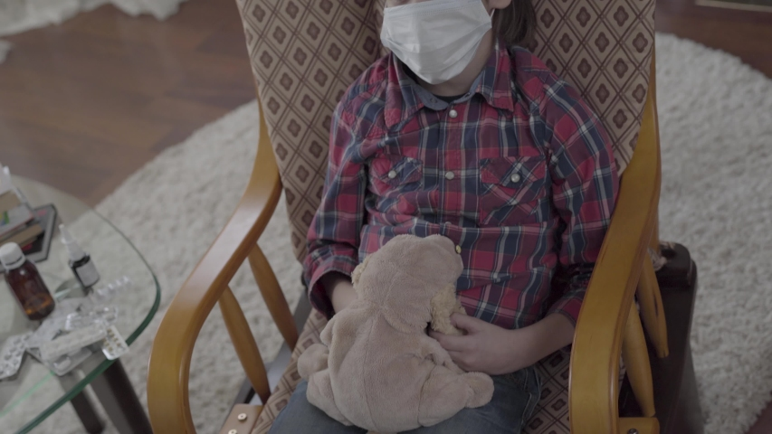 Portrait of a sick boy with a medical bandage on his face swaying in his chair, holding a soft toy in his hands at home. | Shutterstock HD Video #1029813218