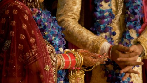 Indian wedding ritual - Bride and Groom holding each others hand. 4K stock footage of Indian wedding ceremony where the bride is giving puffed rice to grooms hand during their wedding ceremony