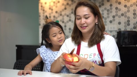 happy Mother teaching daughter peeling red apples together on table in kitchen at home . loving family.  child girl  kissing Mom . cooking . indoors