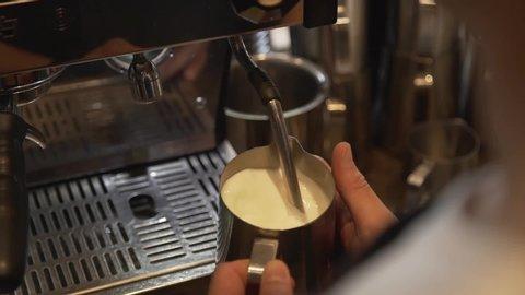 Barista whisk milk in coffee machine with hot steam