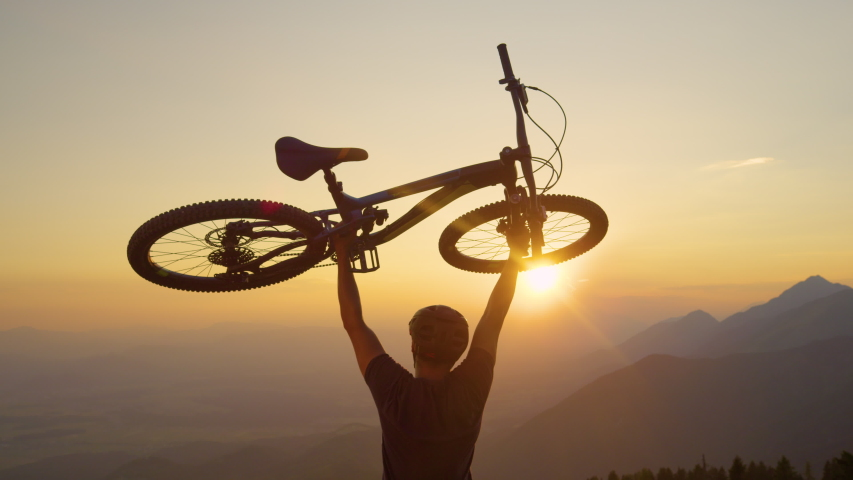 SLOW MOTION, SUN FLARE, CLOSE UP: Happy man lifts his bicycle above his head at sunset after a mountain biking trip in the beautiful mountains. Cheerful tourist celebrates winning a mountain bike ride | Shutterstock HD Video #1029829778