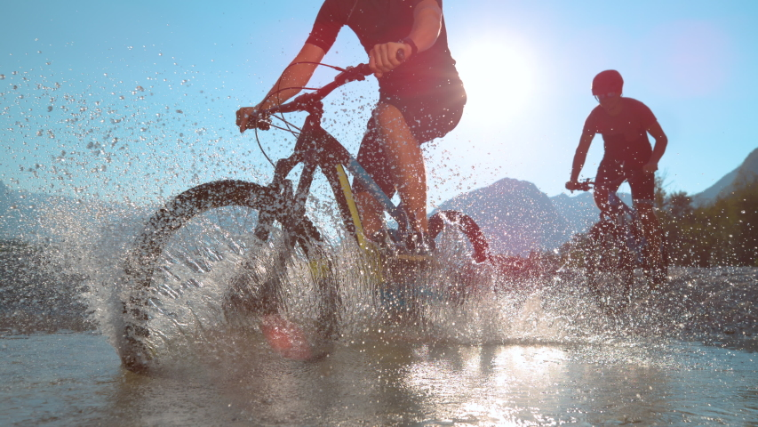SLOW MOTION, LOW ANGLE, LENS FLARE, SILHOUETTE: Friends spraying water at camera while riding bicycles in Soca river on a beautiful summer day. Two guys riding electric bikes in shallow stream water.