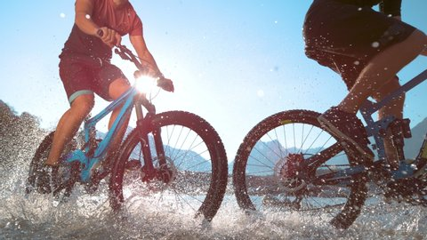 SUPER SLOW MOTION, LENS FLARE, LOW ANGLE: Two unrecognizable fit males spraying glassy stream water at camera while riding high tech electric bicycles across the picturesque Soca valley in Slovenia.