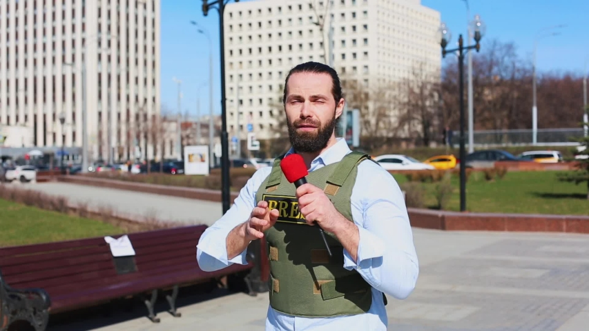 Medium shot, male television journalist in a bulletproof jacket talking to a microphone in front of skyscrapers in the financial district of the city. | Shutterstock HD Video #1029835931