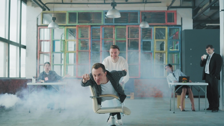 Office chair race. Young businessman is riding a chair in the office like a winner. His colleague helps him. Smoke screen. Office life. Business team. Office party | Shutterstock HD Video #1029848156