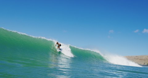 Surfer gets barreled in slow motion, epic ocean wave barreling with surfer riding, surfing adventure island lifestyle