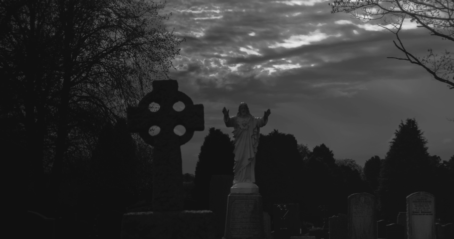 Hyper lapse of clouds moving over jesus statue and celtic cross in dark spooky cemetery at night monochrome