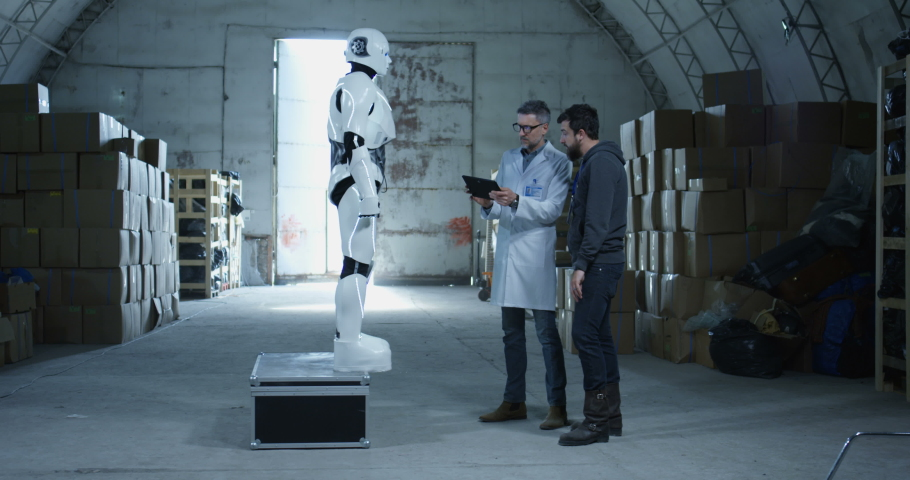 Long shot of engineers testing robot in a warehouse | Shutterstock HD Video #1029885308