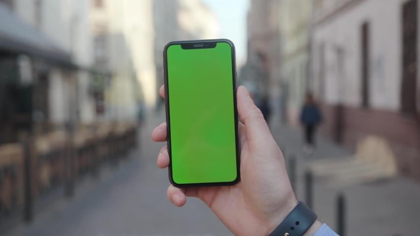 NEW YORK - April 5, 2018: On street man hands holding a smartphone with vertical green screen background city touchscreen wireless business evening cellphone communication device digital internet | Shutterstock HD Video #1029886592