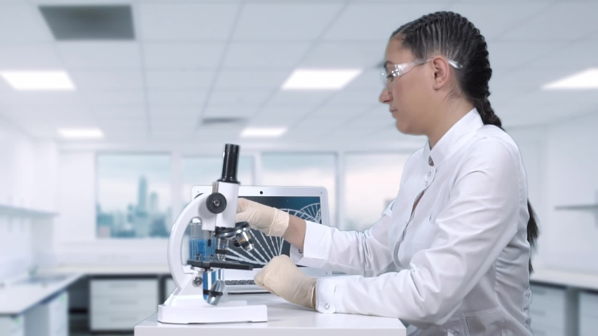 Female laboratory assistant conducts laboratory tests of a blue liquid in a test tube. Scientific laboratory.slow motion