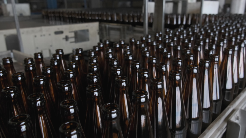 Glass bottle factory. Clean bottles moving on a conveyor belt. Empty brown bottles in a line in factory. Automated production line   Shutterstock HD Video #1029902633
