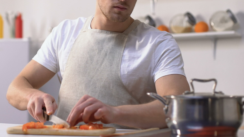 Man trying sauce in pan and screwing up face because of bad taste, cooking   Shutterstock HD Video #1029908249