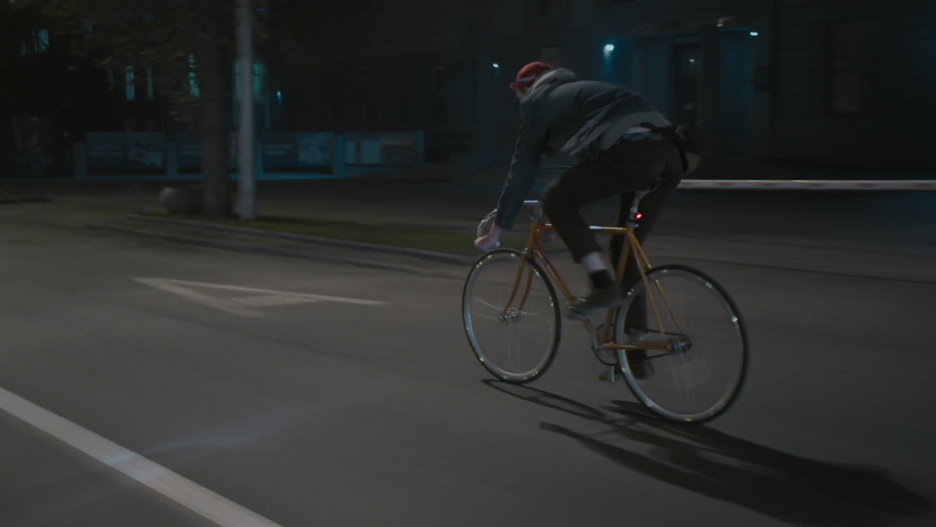 Unrecognizable male cyclist at night city street. Eco-friendly urban transport. Riding a bike with great speed. Active urban lifestyle concept.
