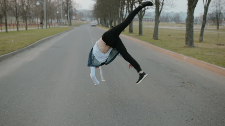 Handheld slomotion shot a young, handsome, energetic guy in black pants and a blue hooded vest performing somersaults and dance on the roadway | Shutterstock HD Video #1029917576