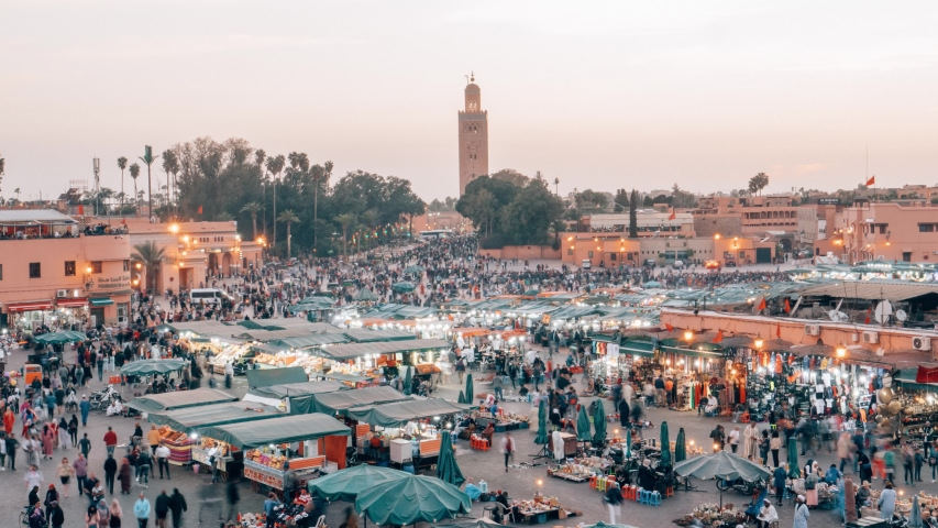 Timelapse stationary above a crowded marketplace Djemaa el Fna in Marrakech Morocco crowded with people buying and selling food and items at sunset turning to night