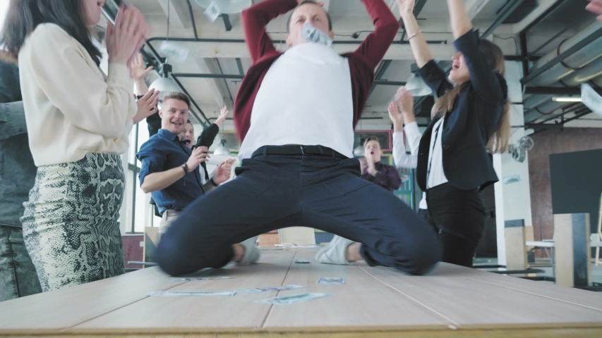 The manager dances on the table, scatters money, accelerates and slide on lap towards the camera. Colleagues celebrate success. Corporate party business team. Trendy office interior. Coworking | Shutterstock HD Video #1029925769
