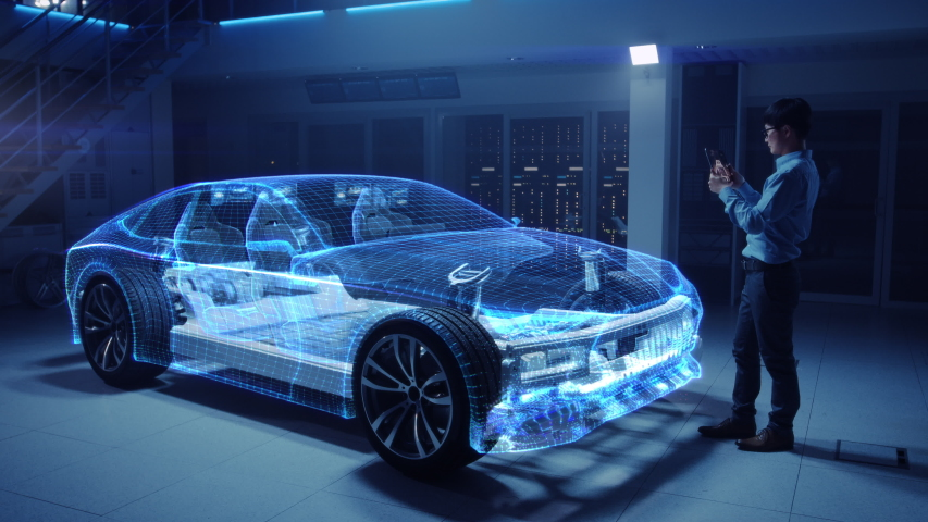 Automotive Engineer Working on Electric Car Chassis Platform, Using Tablet Computer with Augmented Reality 3D Software. Innovative Facility: Vehicle Frame with Wheels Becomes a Solid Virtual Model. Royalty-Free Stock Footage #1029926642