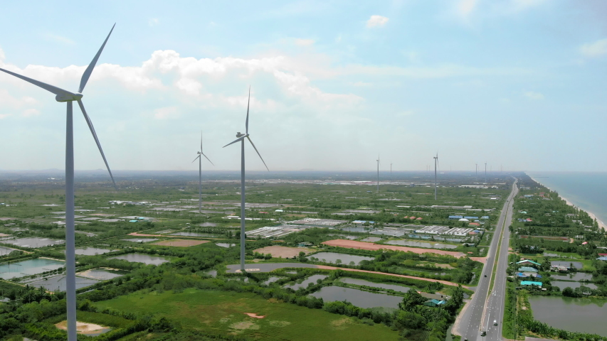 Wind turbine is generating electricity  power for people in a city near sea.Concept of clean power city for no pollution world.Clearly sky with cloudy with road and farming pool in city.Aerial shot. | Shutterstock HD Video #1029932564