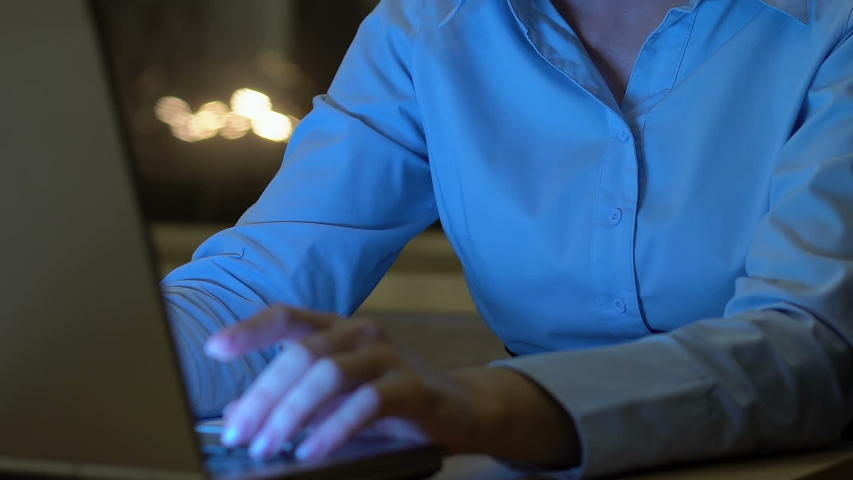 Young female employee working on business project at night in office, career | Shutterstock HD Video #1029933944