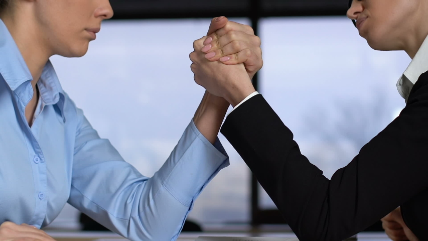 Female colleagues arm wrestling on table, career competition, business conflict