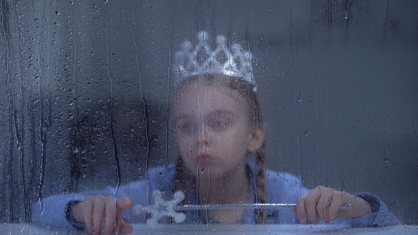 Upset little girl in crown with magic stick sitting alone behind rainy window