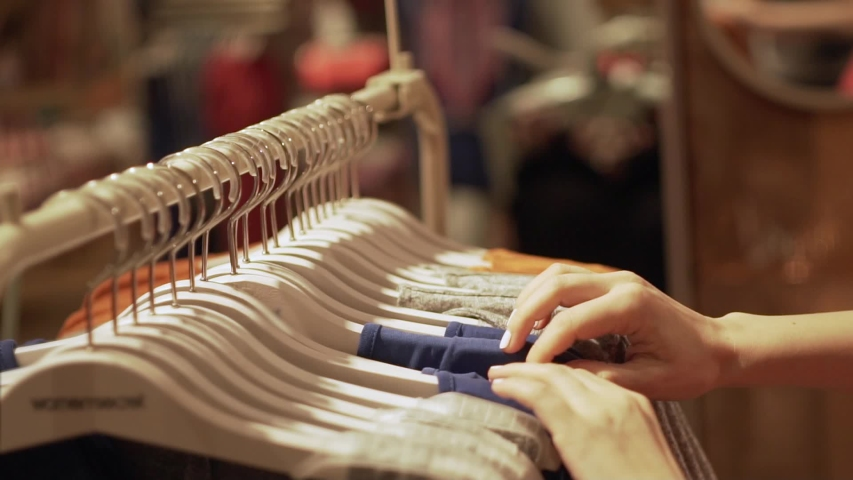 Close up of a girl goes through clothes dresses summer outfits and shop the boutique, the supermarket on the rack, close-up of hands and racks of clothes, shopping | Shutterstock HD Video #1029938756