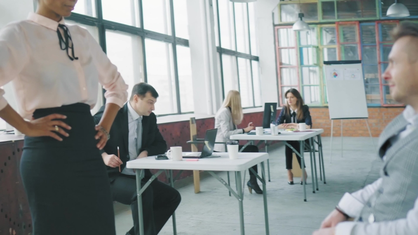 A male manager turns on an office chair to a mixes-race female colleague, winks and flirts with her. She doesn't like it. Modern trendy office interior | Shutterstock HD Video #1029939977