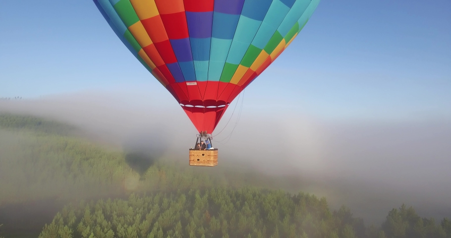 Colorful hot air balloon epic flying above mountain over the fog at sunrise with beautiful sky background - Aerial drone view