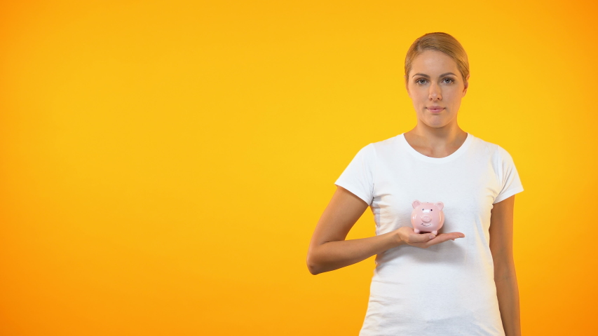 Happy female covering piggybank by hand, safe bank deposit, account insurance | Shutterstock HD Video #1029942779