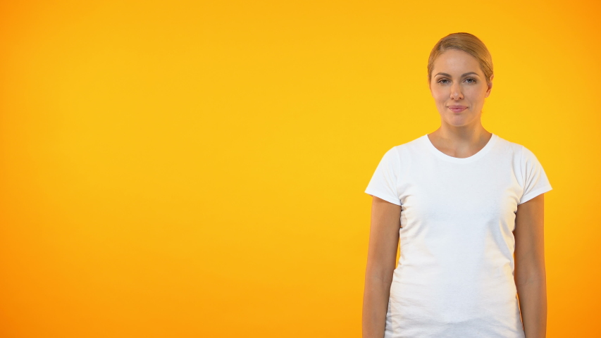 Young smiling woman presenting template on orange background, announcement | Shutterstock HD Video #1029942797