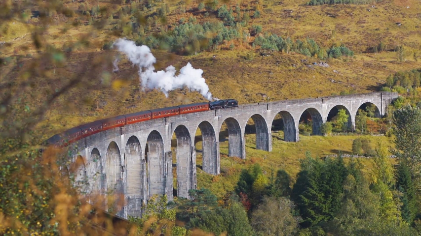 A HIGH ANGLE VIEW of a stream train crossing a viaduct in the beautiful countryside. SLOW MOTION, STATIC SHOT.