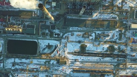 Top view aerial shot of an old outdated factory, as white smoke rises from a chimney polluting the air, causing global warming