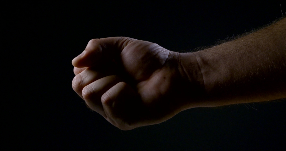 A man squeezes his hand in the dark. strong male grip | Shutterstock HD Video #1029963263