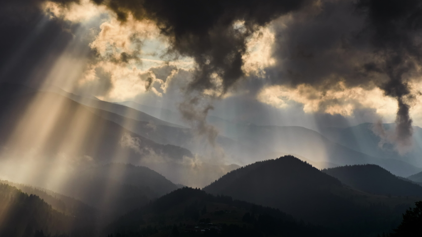 Timelapse of sun rays emerging though the dark storm clouds in the mountains  #1029971897